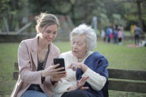 girl helping senior with phone